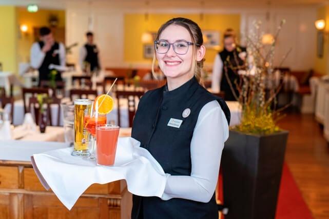 lächelnde Frau mit Tablett im Restaurant