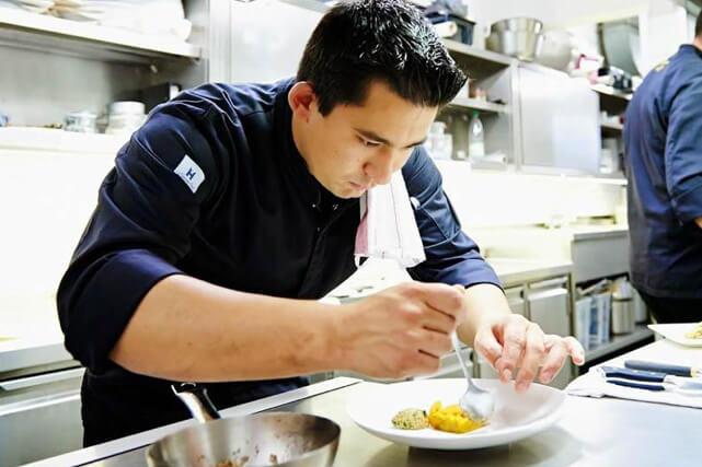 konzentrierter Koch beim Anrichten