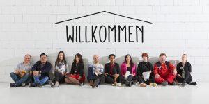 Lächelnde Menschen lehnen an Wand mit Willkommen-Schriftzug