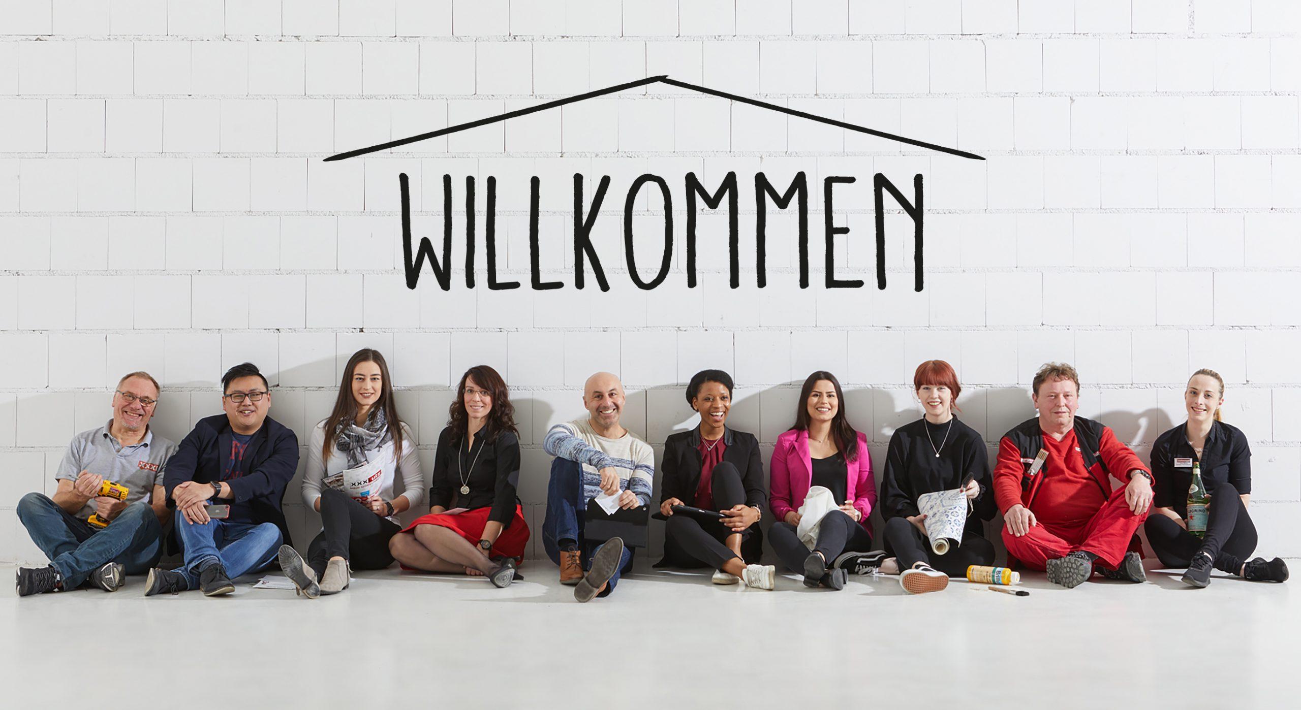 """Team vor Ziegelwand mit """"Wilkommen"""" beschriftet"""
