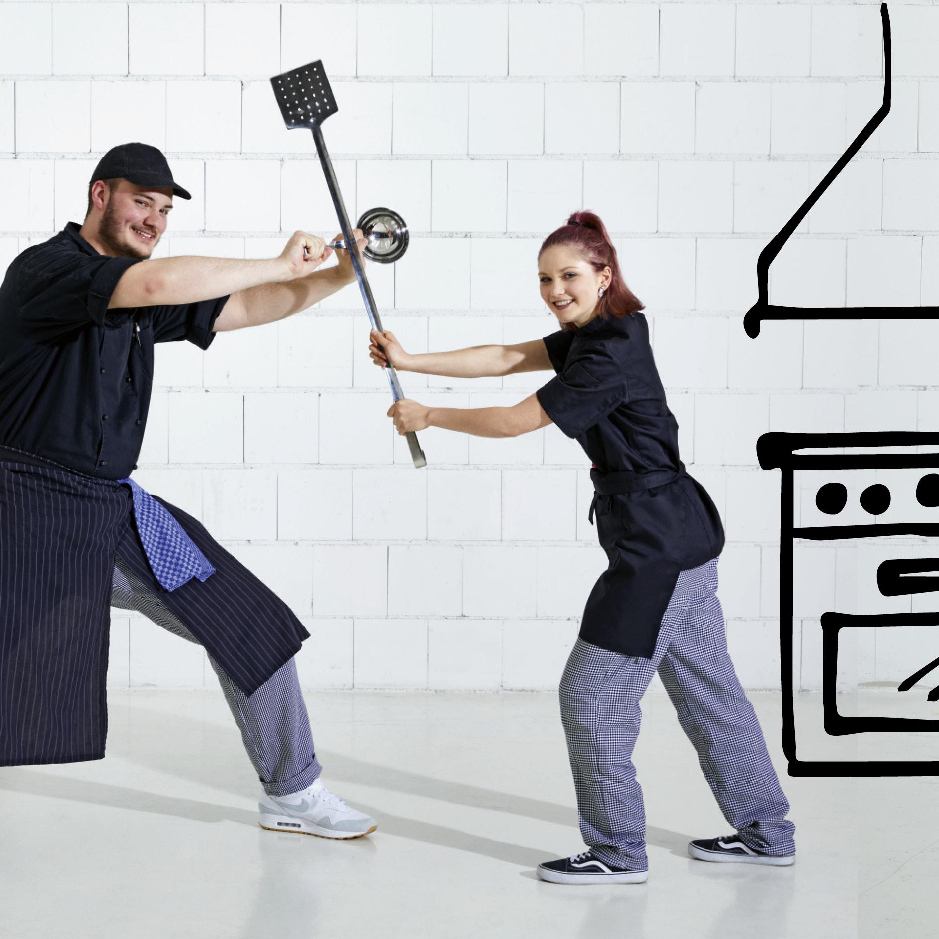 Gastronomiepersonal kämpft im Scherz mit Küchenutensilien